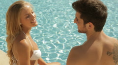 young couple sitting by side of pool - stock footage