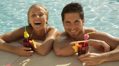 young couple laughing with drinks at side of pool - stock footage