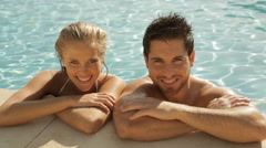 young couple laughing at side of pool - stock footage