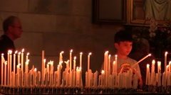 A young guy lighting a candle at church Stock Footage