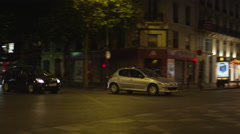 Wide panning shot of traffic on busy city street at night / Paris, France - stock footage