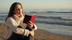 Woman sitting on beach reading book. Stock Footage