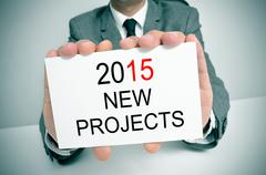 Man in suit with a signboard with the text 2015 new projects Stock Photos