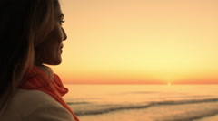 Woman looking at ocean in sunset. - stock footage