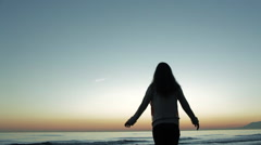 Carefree woman looking at ocean in sunset. Stock Footage