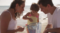 Parents and daughter with fishing net at the beach. - stock footage
