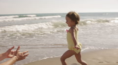 Mother and daughter playing and hugging at the beach. - stock footage