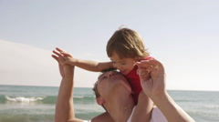 Happy little girl on her father's shoulders at beach. Stock Footage