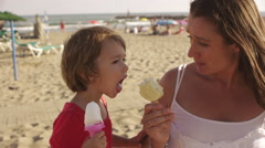 Mother and daughter eating popsicles at the beach. Stock Footage
