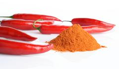 studio shot of spicy chilli peppers and stack of cayenne pepper isolated on a - stock photo