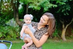 Smiling mother and baby playing in park Stock Photos