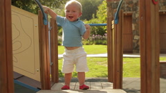 Young toddler walking on play structure. Stock Footage