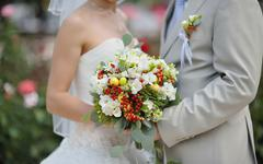 Bride holding wedding flower bouquet of white roses Stock Photos