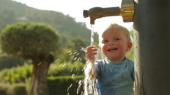 Slow motion of toddler playing with water in park. - stock footage