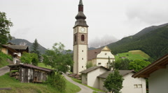 Low angle panning shot of church and clock tower in rural village / Funes, Italy Stock Footage