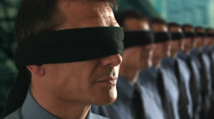 Businessman in a line-up removing his blindfold. Stock Footage