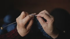 The old woman sits at home and knits garments. Close up Stock Footage