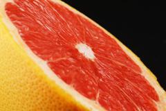 close up shot of half of grapefruit on white background - stock photo