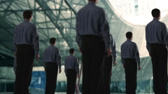 Group of businessmen, on of them turns to camera. - stock footage