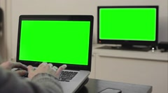 Laptop and tv green screen man typing on computer - 1080p Stock Footage