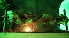 Meat roasting on a spinning rotisserie with smoke Stock Footage