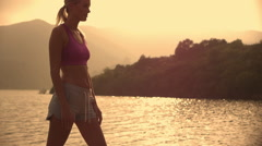 Woman stretching on jetty beside water. Stock Footage