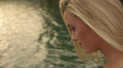 Blond woman's face as she sits beside water. Stock Footage