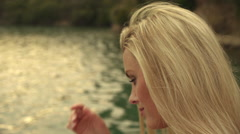 Blond woman's face as she sits beside water. - stock footage