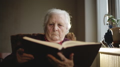 Old human reading a book. Stock Footage