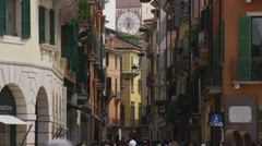Wide panning shot of crowd in street looking at clock tower / Verona, Italy Stock Footage