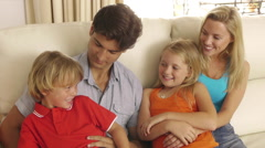 Family sitting on couch together in living room. Stock Footage