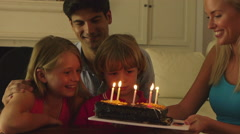 Boy blowing  candles on birthday cake. Stock Footage