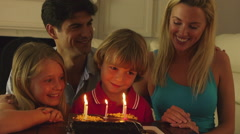 Boy blowing out candles on birthday cake. - stock footage