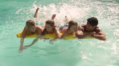 Family playing in swimming pool on lilo. Stock Footage