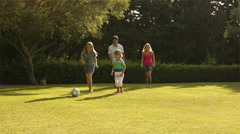 Slow motion shot of family playing soccer. - stock footage