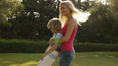 Mother playing with her son in garden. - stock footage