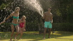 Family playing in sprinkler in garden. Stock Footage