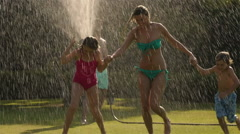 Family playing in sprinkler in garden. - stock footage