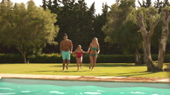 Slow motion of family jumping in pool. - stock footage