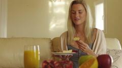 Woman eating breakfast on sofa. - stock footage