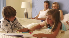 Children drawing in bed while parents watch. - stock footage