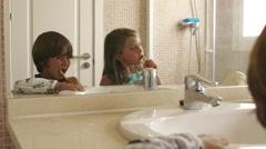 Children brushing their teeth in bathroom. - stock footage