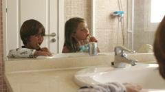 Children brushing their teeth in bathroom. - stock footage