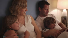 Family reading in bed together. - stock footage