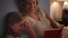 Mother and daughter reading in bed. - stock footage