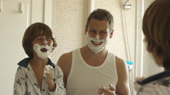 Father and son with shaving cream on their faces. Stock Footage