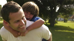 Father giving son a piggy back ride. Stock Footage