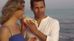 Couple listening to conch shell by sea. - stock footage