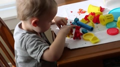 Toddler playing with play dough Stock Footage