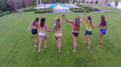 Group Of Fun Teen Girls Run And Jump Into Swimming Pool (Drone Shot) - stock footage